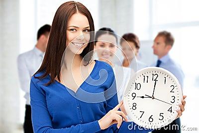 Businesswoman pointing at alarm clock