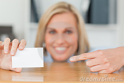 Businesswoman pointing at a card crouching