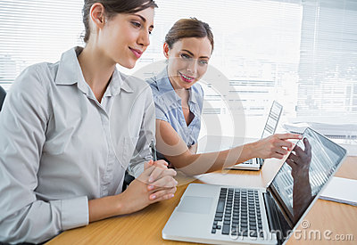 Businesswoman pointing to something on laptop for colleague