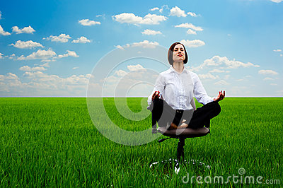Businesswoman practicing yoga at the meadow