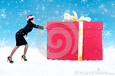 Businesswoman push christmas gift in snow