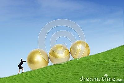 Businesswoman push golden eggs on hill