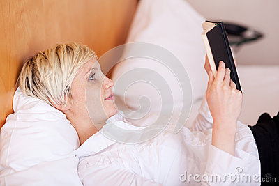 Businesswoman Reading Diary While Lying On Bed