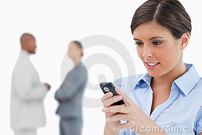 Businesswoman reading text message with associates