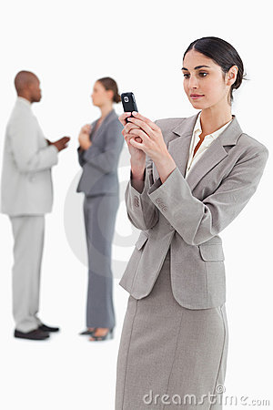 Businesswoman reading text message with colleagues behind