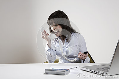Businesswoman Screaming Into Phone Receiver
