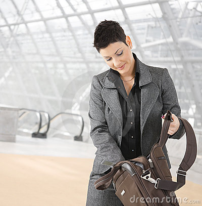 Businesswoman searching in laptop bag