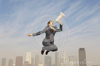 Businesswoman Shouting Into Megaphone Above City