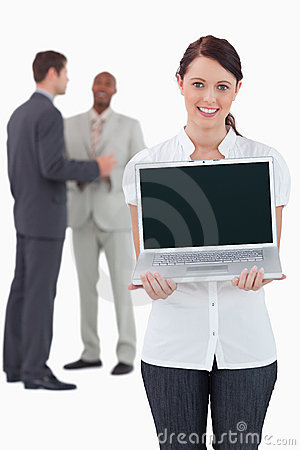 Businesswoman showing laptop with colleagues