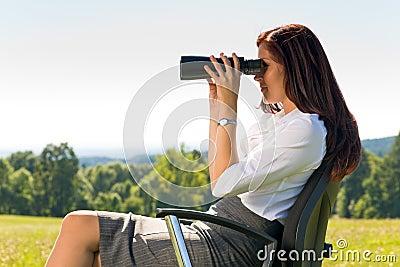 Businesswoman sit in sunny meadow seek binocular