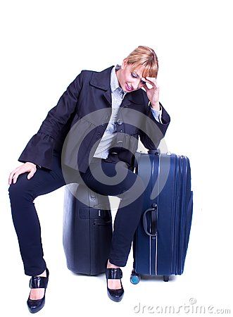 Businesswoman sits on black suitcase and waiting