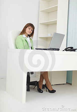 Businesswoman sits at light office with laptop
