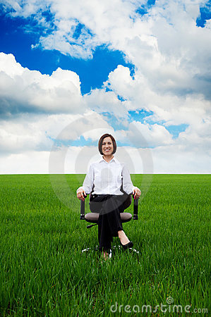 Businesswoman sitting on chair over green field