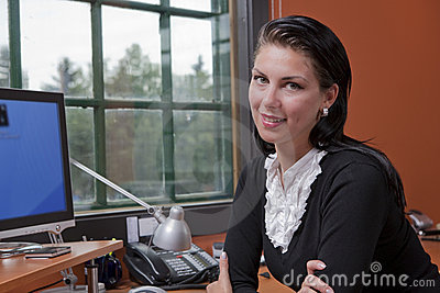 Businesswoman Sitting At Computer At Her Desk