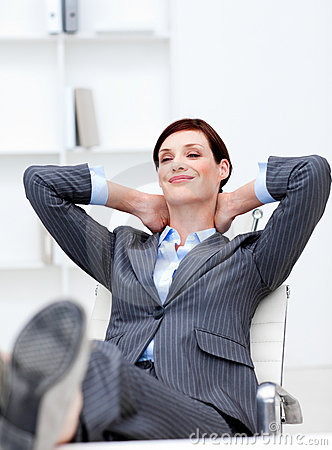 Businesswoman Sitting In Office With Feet On Desk Royalty
