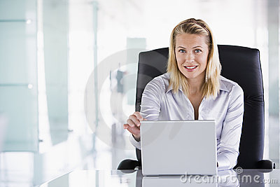 Businesswoman sitting in office with laptop