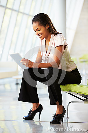 Businesswoman Sitting On Sofa In Office Using Digital Tablet