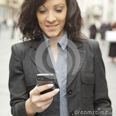 Businesswoman with smartphone, phone in focus
