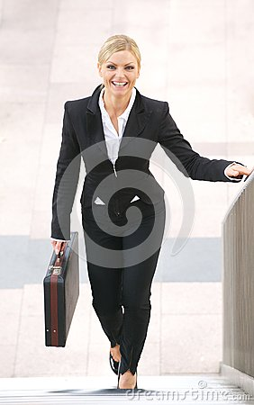 Businesswoman smiling and walking upstairs with briefcase