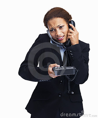 Businesswoman speaking over two telephones