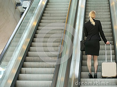 Businesswoman standing on escalator with travel bags