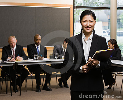 Businesswoman standing in front of co-workers