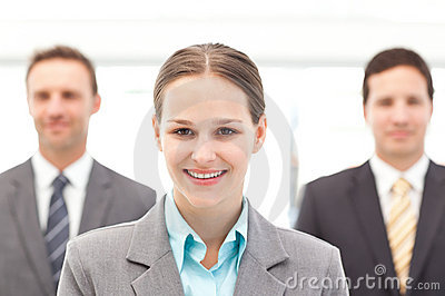 Businesswoman standing in front of two businessmen
