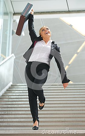 Businesswoman standing on staircase with arm raised in celebration