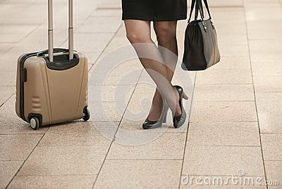 Businesswoman standing with travel bags on city sidewalk