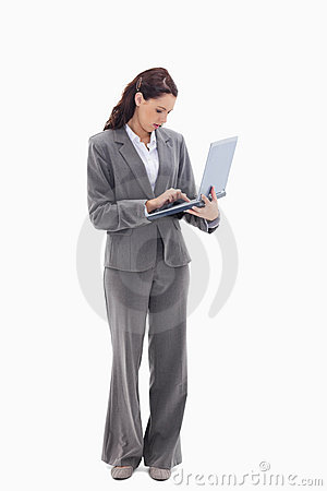 Businesswoman standing and typing on a laptop