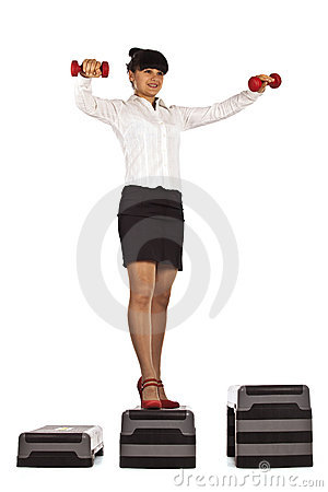 Businesswoman stands  up with dumbbells