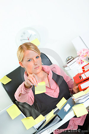 Businesswoman stretches out hand with sticky notes