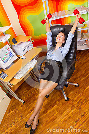 Businesswoman stretching with dumbbells