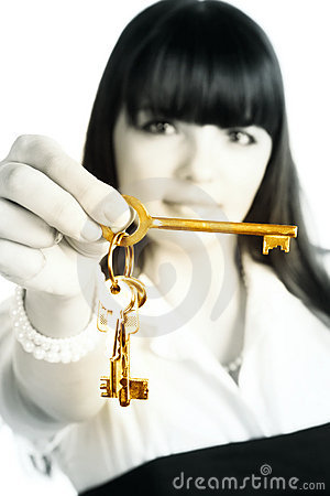 Businesswoman stretching gold keys