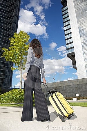 Businesswoman with suitcase and business building