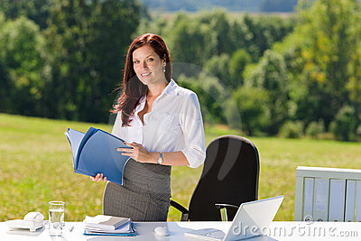 Businesswoman in sunny nature office hold folders