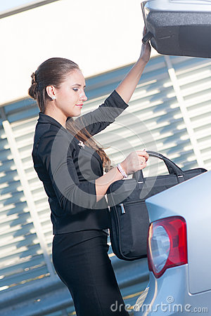 Businesswoman takes bag out from the car