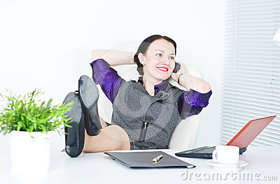 Businesswoman talk on phone with legs on the table