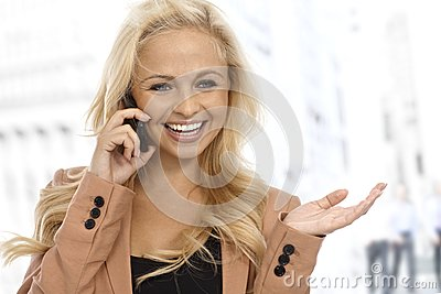 Businesswoman talking on cellphone on street