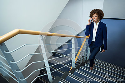 Businesswoman talking on mobile phone while climbing steps Stock Photo