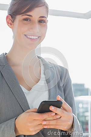 Businesswoman texting on smartphone and smiling at camera