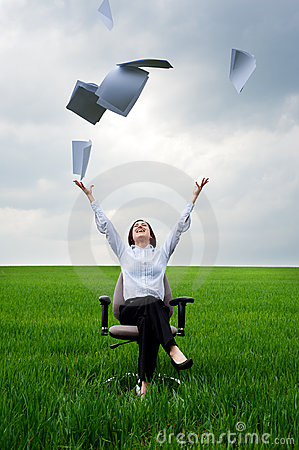 Businesswoman throwing away documents at the field