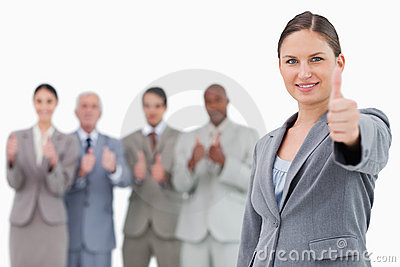 Businesswoman with thumb up and colleagues behind her