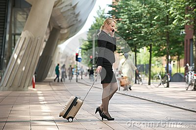 Businesswoman traveling with luggage and mobile phone