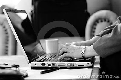 Businesswoman Typing in Hotel Atrium (BW)