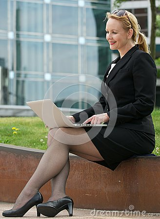 Businesswoman typing on laptop outdoors in the cit