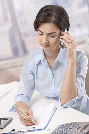 Businesswoman using cellphone in office