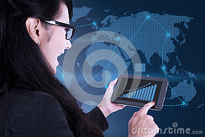 Businesswoman using digital touchpad on world map background