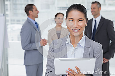 Businesswoman using her tablet pc while colleagues talking toget