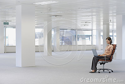Businesswoman Using Laptop On Chair In Empty Office